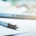 un stylo en gros plan sur fond flou où l'on distingue un cahier et un ordinateur portable